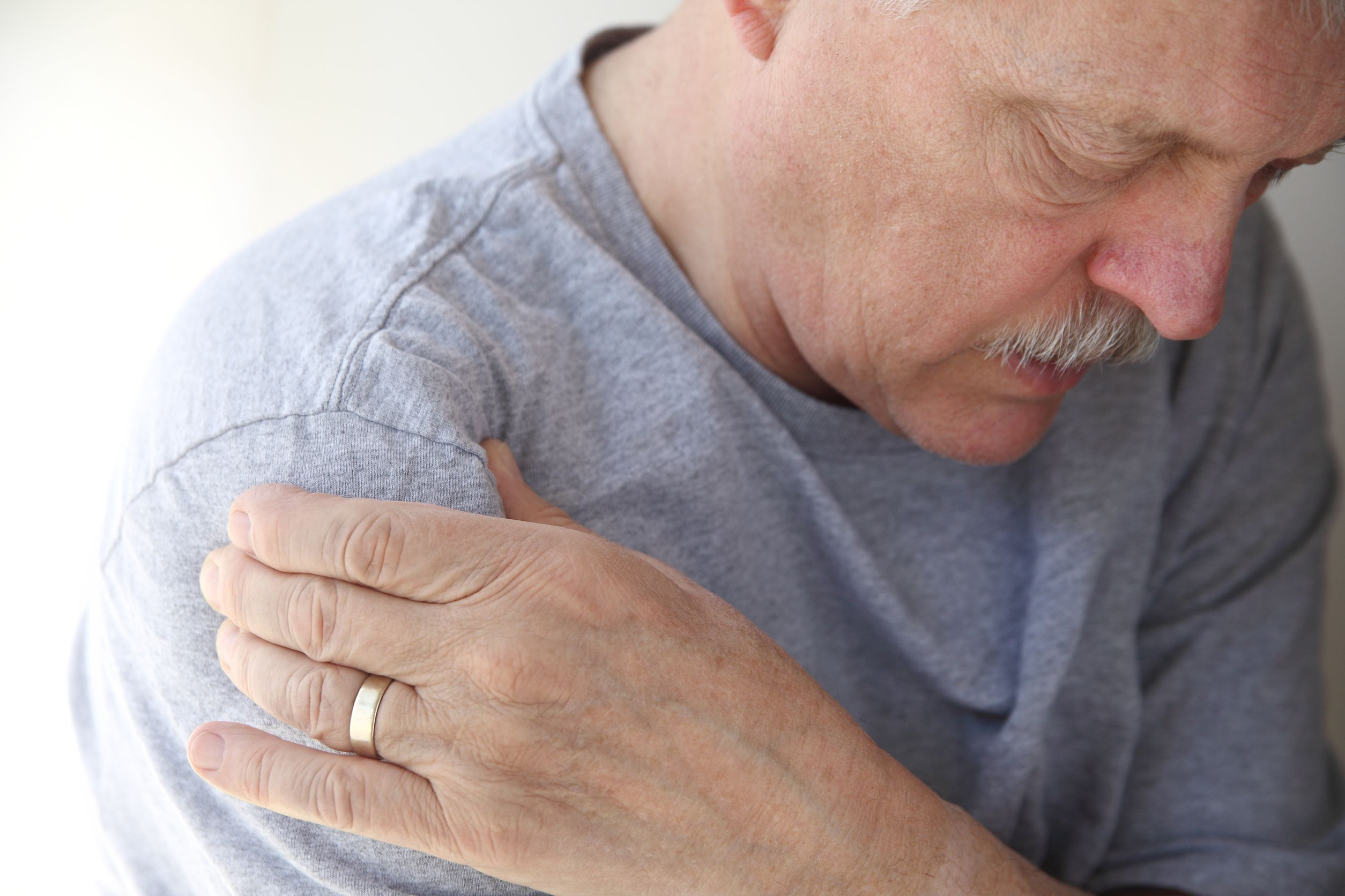 12987358 – man suffering from aching shoulder